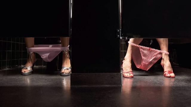 Girl peeing in toilet stall